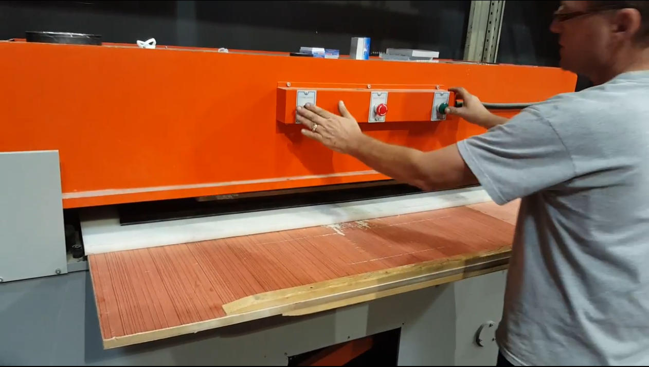 a man showing how to cut using a 40 ton beam press machine